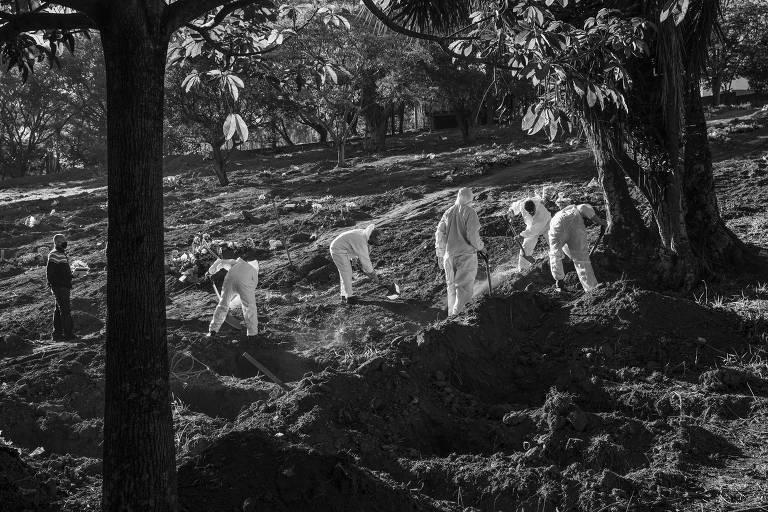 Sepultadores enterram vítima de Covid-19 no cemitério São Luiz, na zona sul de São Paulo. Foram abertas mais de 3.000 novas covas para receber as vítimas da pandemia neste cemitério